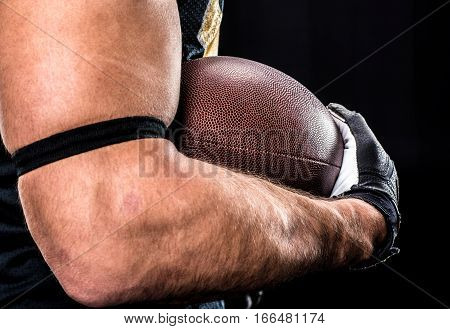 Partial view of muscular football player holding rugby ball