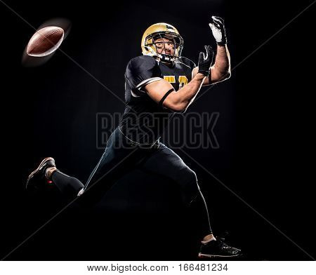 Full length view of american football player in protective sportswear catching ball on black