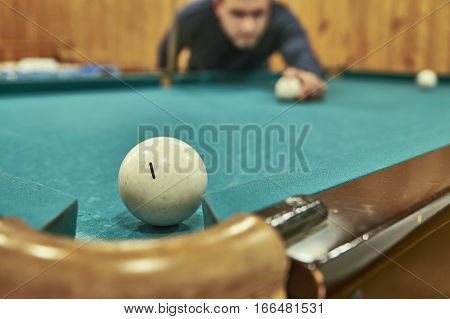 Middle-aged man playing billiards in the club.