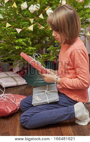 Teenage girl unwrapping Christmas gifts near Christmas tree sitting on the floor
