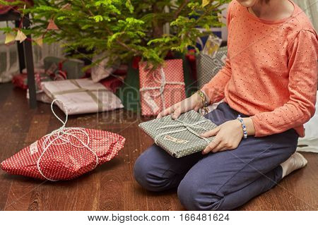 Teenage girl unwrapping Christmas gifts near Christmas tree sitting on the floor