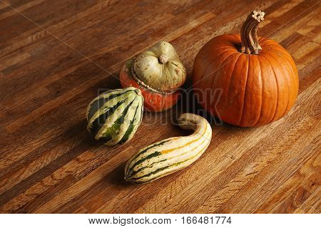 Mixed different pumpkins isolated on wooden table in center