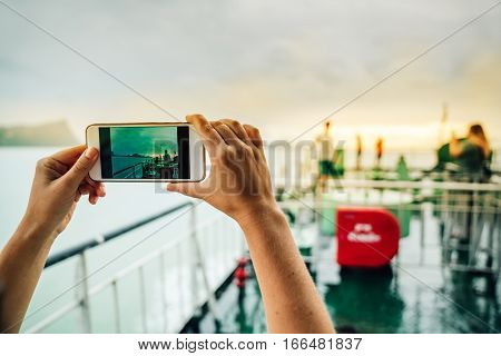 woman makes the photo on his smartphone. close-up of the hands of the girl with the phone the screen setting sun from the ferry deck.