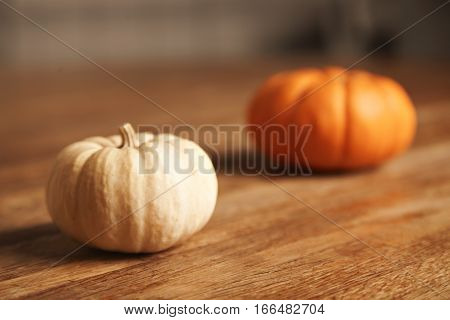 Close focus on small white pumpkin next to unfocused orange big one, both isolated on wooden table in artisan kitchen