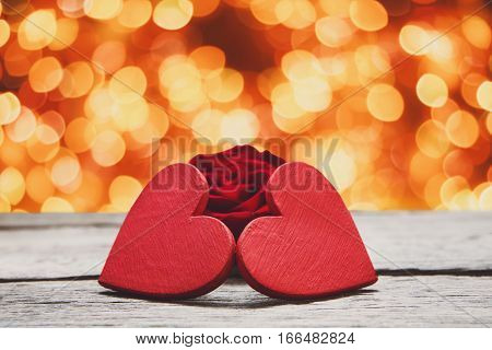 Valentine background with handmade glitter hearts and rose flower on rustic wood with holiday lights bokeh background. Happy lovers day party invitation card mockup, copy space