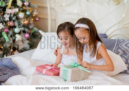 Child girls wake up in their bed near decorated Christmas tree in beautiful room in the holiday morning, enjoying with presents