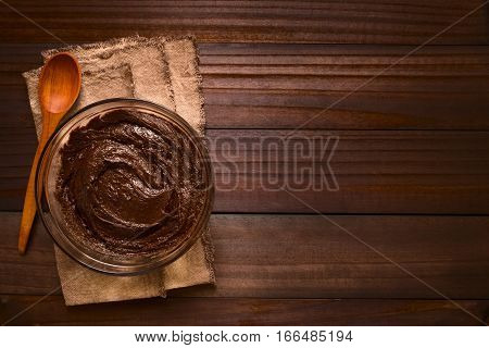 Basic brownie chocolate cake or cookie dough in glass bowl with wooden spoon on the side photographed overhead on dark wood with natural light (Selective Focus Focus on the top of the dough)