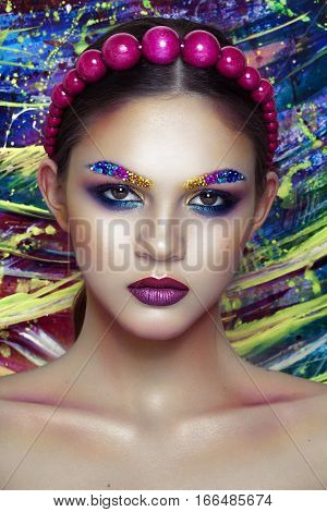 Fashion Beauty . Bright art Make-up with strasses on face, portrait on painting colorful background.