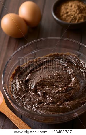 Basic homemade brownie chocolate cake or cookie dough in glass bowl with cocoa powder and eggs in the back photographed on dark wood with natural light (Selective Focus Focus one third into the image)