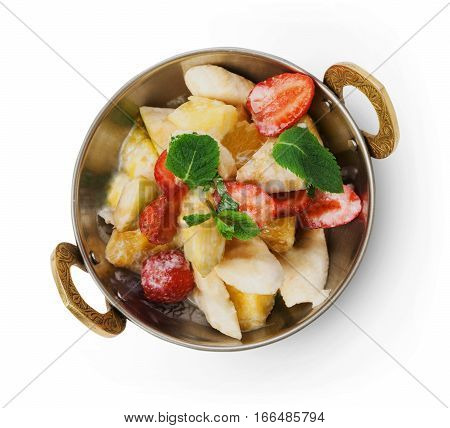 Vegan and vegetarian dish, fresh fruit and strawberry salad in copper bowl closeup isolated on white background, top view. Indian restaurant healthy meal, dessert. Eastern local food.
