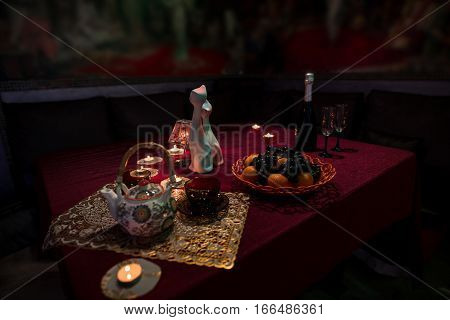 Table laid for tea with two beautiful cups, teapot, a bottle of champaigne with two glasses, some fruit, candles and porcelain figurines on red table cloth in sauna restroom