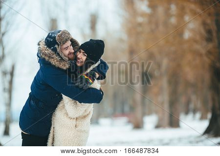 guy hugging his girlfriend in a snowy park