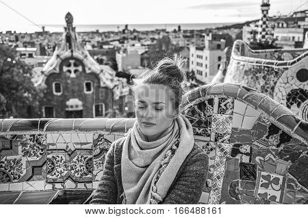 Relaxed Woman At Guell Park In Barcelona, Spain Sitting On Bench