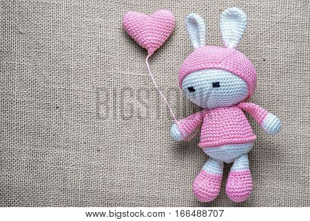 Crochet Children's Soft Toy Bunny Wielding Knitted Balloon On The Sackcloth Background, With Copy Sp