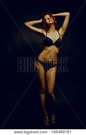 Seductive girl in underwear posing over black background