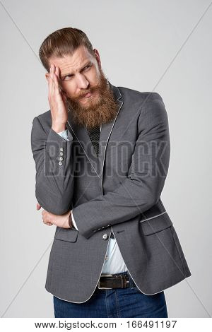Sullen disliking hipster business man with hand on head looking to side