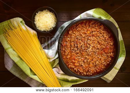 Homemade bolognese sauce made of fresh tomatoes onion carrot garlic and mincemeat served in rustic bowl uncooked spaghetti and grated cheese on the side photographed overhead on dark wood with natural light