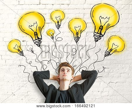 businessman standing against concrete wall with lighbulb drawings