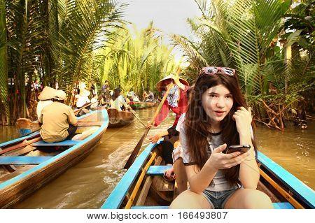 Mekong river Vietnam December 27 2016: Unidentified teen tourist girl on Mekong river hike amazed make pictures in Vietnam December 27 2016.