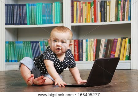 Cute white Eight months old todler baby playing with tablet perconal computer on the floor