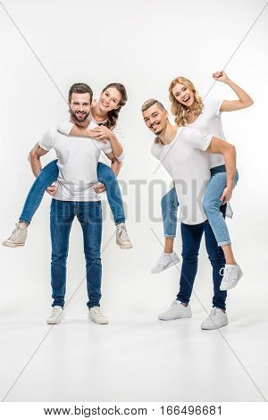 Happy couples piggybacking and looking at camera on white