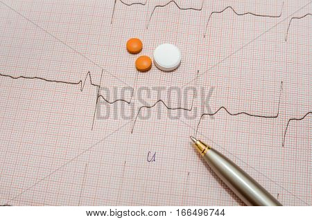 Electrocardiogram graph report with pills and pen