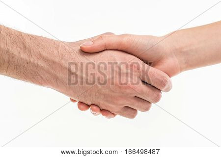 Close-up view of male and female hands handshaking on white