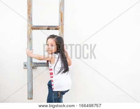 Little Asian Girl Kid Climbs The Stairs -fire Escape , The White Wall Background