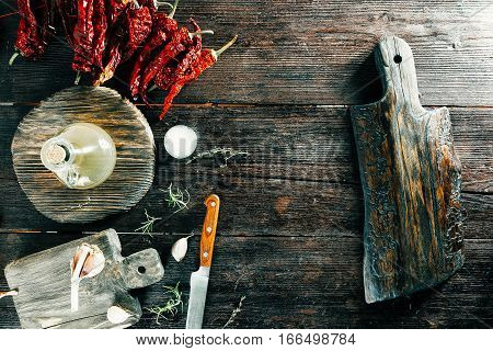 Red dried chili, rosemary and condiments on wooden boards. One cutting board for frame