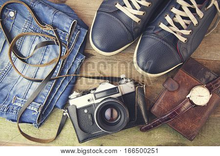 keds jinse watch wallet and camera on wooden background
