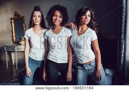 Beautiful smiling girls having fun in white shirts on the bed. t-shirt mock-up.