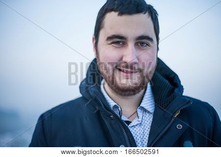 Portrait of a young brutal sarcastic man looking at camera