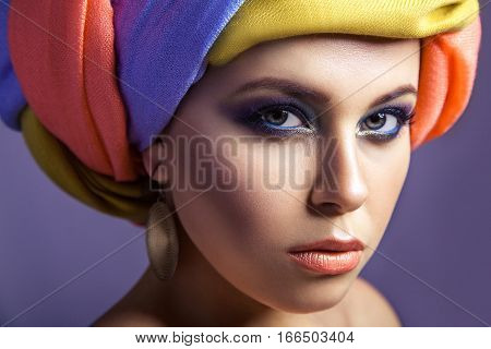Beautiful Woman With Colored Headwear And Blue Makeup.