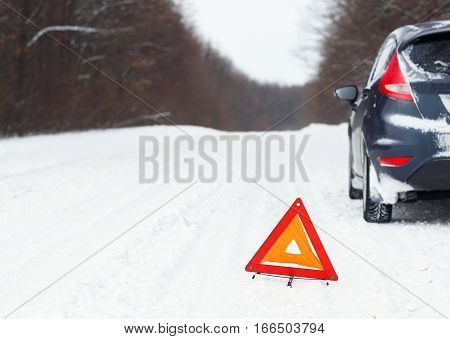 Transportation winter and vehicle concept - closeup of red warning triangle with a broken down car