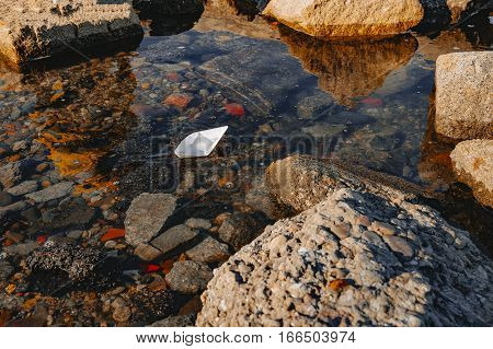 paper boat on the water between rocks. paper ship sailing
