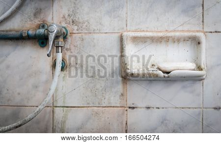 Soap and valve of shower in dirty bathroom.
