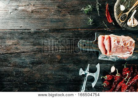 Raw loin on wooden board, meat chopper and spices