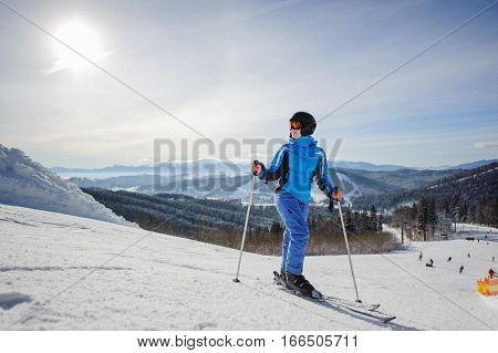 Young Beautiful Female Skier On The Middle Of Ski Slope