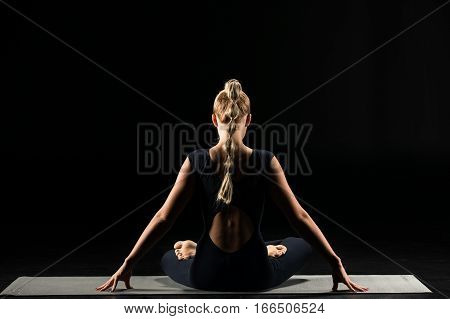 Rear view of woman practicing yoga sitting in lotus position on yoga mat