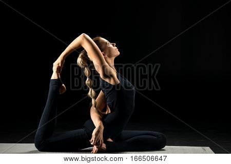 Woman practicing yoga and sitting in One Legged King Pigeon Posture (Eka Pada Rajakapotasana)