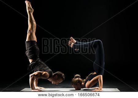 Couple performing acroyoga doing handstand Ganda Bherundasana or Formidable Face Posture