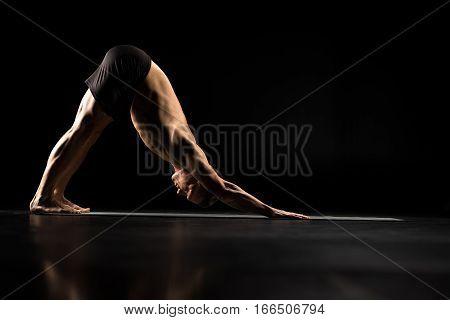 Man performing Adho Mukha Svanasana or Downward Facing Dog Pose