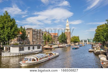 AMSTERDAM, NETHERLANDS - SEPTEMBER 18, 2016: Tourist cruiseboat and historical tower in Amsterdam, Holland