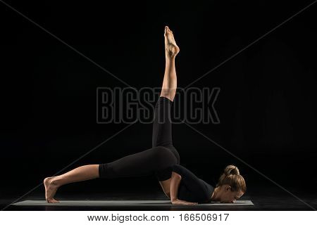 Woman performing variation of Ashtanga Namaskara asana on yoga mat