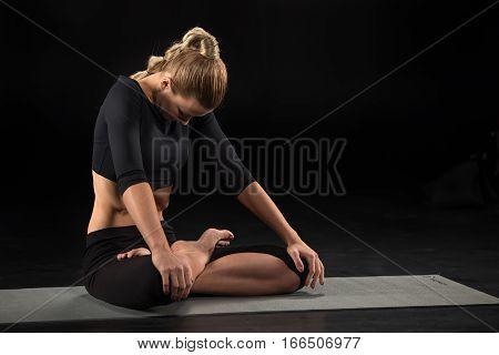Woman performing Maha Bandha technique on yoga mat