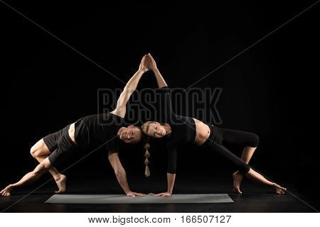 Couple performing acroyoga side plank pose on yoga mat