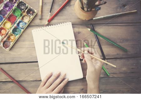 woman hand brush and paper with pencil on table