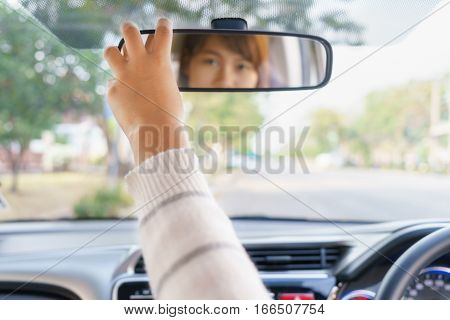 Woman hand adjusting rear view mirror of her car