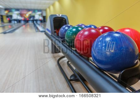 Bowling background. Interior of bowling alley lane with balls return machine closeup, selective focus on blue ball