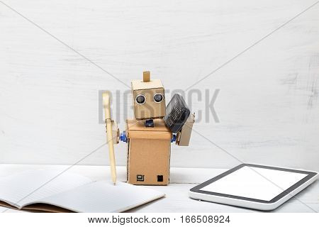 The robot holds a pen and the phone is near laptop. Work
